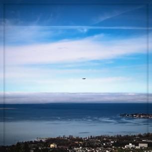 Blick auf den See mit Zeppelin und Wolken. Bregenz und ein Teil von Lindau Insel sind zu sehen.