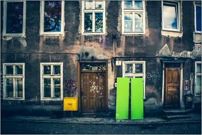 Grüne Tür(en) an altem Haus mit gelben Kasten